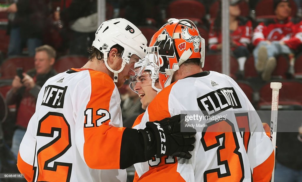 Brian Elliott #37 of the Philadelphia Flyers is congratulated by Michael Raffl #12 after defeating the New Jersey Devils at Prudential Center on January 13, 2018 in Newark, New Jersey.