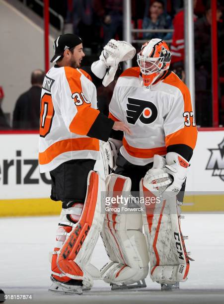 Brian Elliott of the Philadelphia Flyers is congratulated by teammate Michal Neuvirth following a victory over the Carolina Hurricanes during an NHL...
