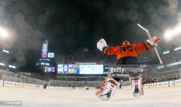 Brian Elliott of the Philadelphia Flyers skates away from his net to celebrate with his teammates after defeating the Pittsburgh Penguins 43 in...
