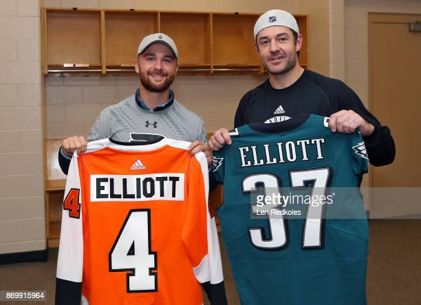 Brian Elliott of the Philadelphia Flyers takes part in a jersey swap with Jake Elliott of the Philadelphia Eagles following a NHL game against the...