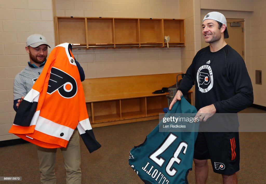 Brian Elliott #37 of the Philadelphia Flyers takes part in a jersey swap with Jake Elliott #4 of the Philadelphia Eagles following a NHL game against the Arizona Coyotes on October 30, 2017 at the Wells Fargo Center in Philadelphia, Pennsylvania.