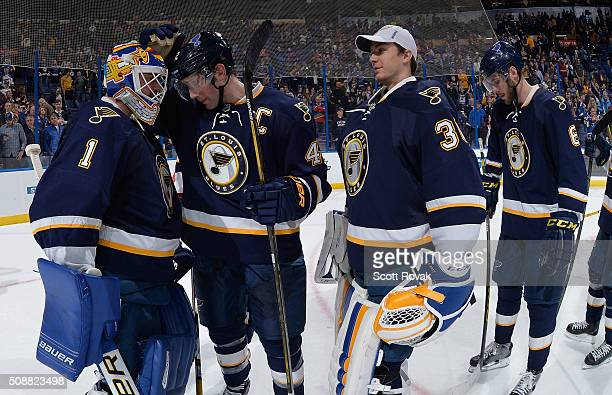 Brian Elliott of the St Louis Blues is congratulated by teammates David Backes and Pheonix Copley after beating the Minnesota Wild at the Scottrade...