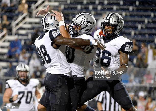 Brian Espanet of the New Hampshire Wildcats celebrates with teammate after making a catch for a touchdown in the first half against the FIU Golden...