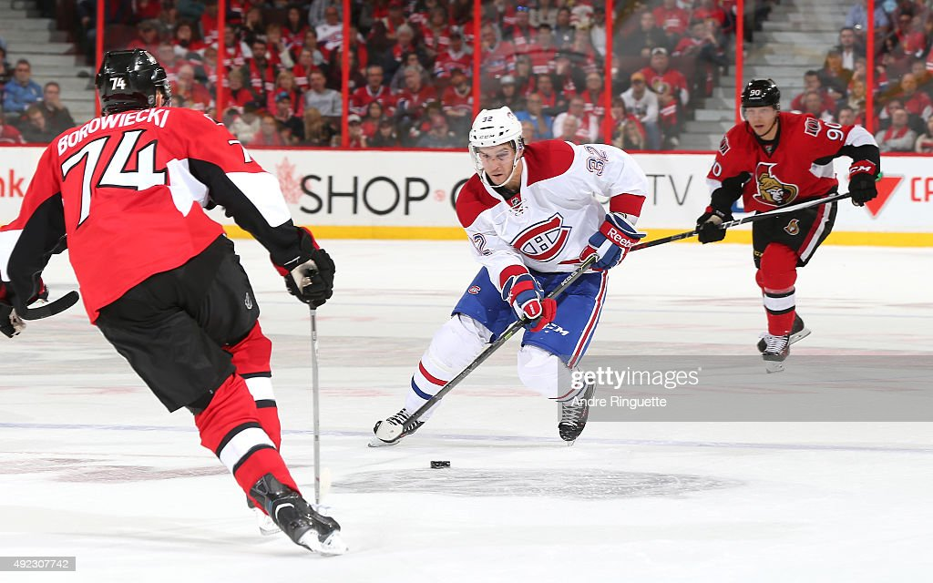 Brian Flynn #32 of the Montreal Canadiens skates up ice with the puck against Mark Borowiecki #74 and Alex Chiasson #90 of the Ottawa Senators at Canadian Tire Centre on October 11, 2015 in Ottawa, Ontario, Canada.