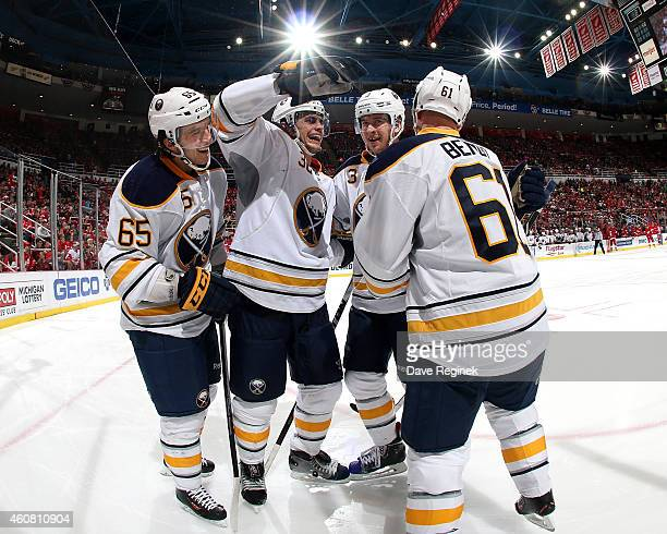 Brian Flynn Patrick Kaleta and Mark Pysyk of the Buffalo Sabres congratulate teammate Andre Benoit after scoring a goal during a NHL game against the...