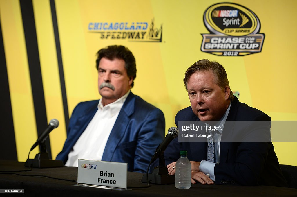 Brian France, chairman & CEO of NASCAR, and Mike Helton, president of NASCAR, speak during a press conference following practice for the NASCAR Sprint Cup Series Geico 400 at Chicagoland Speedway on September 13, 2013 in Joliet, Illinois. NASCAR announced that Jeff Gordon, driver of the #24 Drive To End Hunger Chevrolet, would be added as a 13th driver in the Chase for the Sprint Cup.