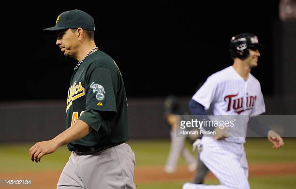 Brian Fuentes of the Oakland Athletics walks off the field as Joe Mauer of the Minnesota Twins heads home to score after Josh Willingham hit a...