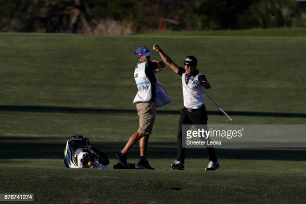 Brian Gay of the United States celebrates with his caddie after holing out on the fairway of the 18th hole during the final round of The RSM Classic...