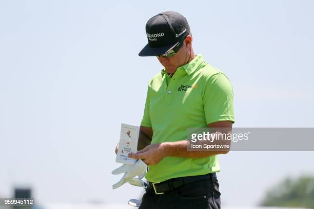 Brian Gay of the United States looks over his yardage book before hitting his tee shot on during the second round of the 50th anniversary AT&T Byron...