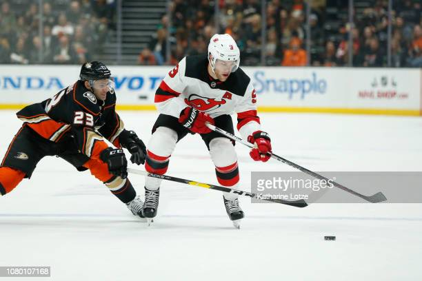 Brian Gibbons of the Anaheim Ducks and Taylor Hall of the New Jersey Devils fight for control of the puck at Honda Center on December 09 2018 in...