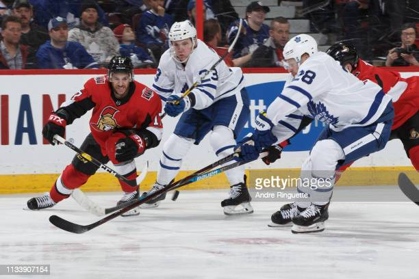 Brian Gibbons of the Ottawa Senators battles for puck possession against Travis Dermott and Connor Brown of the Toronto Maple Leafs at Canadian Tire...
