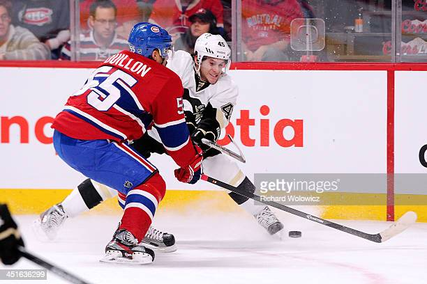 Brian Gibbons of the Pittsburgh Penguins passes the puck in front of Francis Bouillon of the Montreal Canadiens during the NHL game at the Bell...