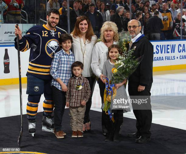 Brian Gionta of the Buffalo Sabres poses with his family during a ceremony honoring him prior to playing in his 1000th career NHL game against the...