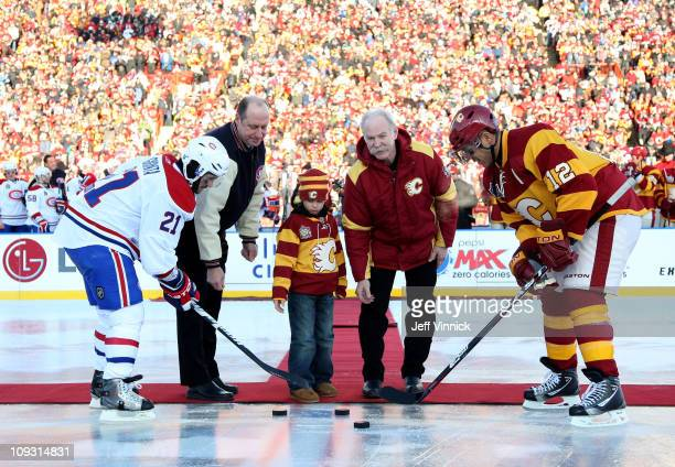 Brian Gionta of the Montreal Canadiens and Jarome Iginla of the Calgary Flames take the ceremonial opening faceoff as Bob Gainey of the Montreal...