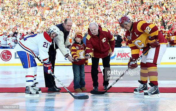 Brian Gionta of the Montreal Canadiens and Jarome Iginla of the Calgary Flames prepare to take the ceremonial opening faceoff as Bob Gainey of the...