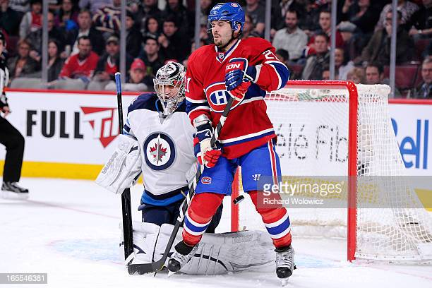 Brian Gionta of the Montreal Canadiens deflects the puck past Ondrej Pavelec of the Winnipeg Jets to score during the NHL game at the Bell Centre on...