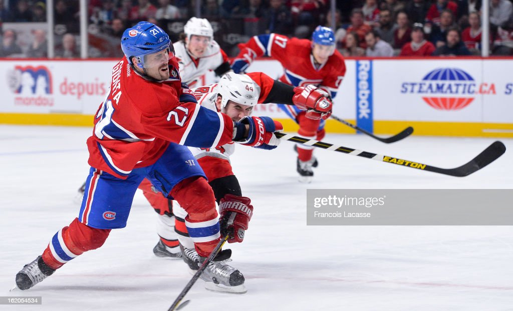 Brian Gionta #21 of the Montreal Canadiens fires the puck past Jay Harrison #44 of the Carolina Hurricanes during the NHL game on February 18, 2013 at the Bell Centre in Montreal, Quebec, Canada.