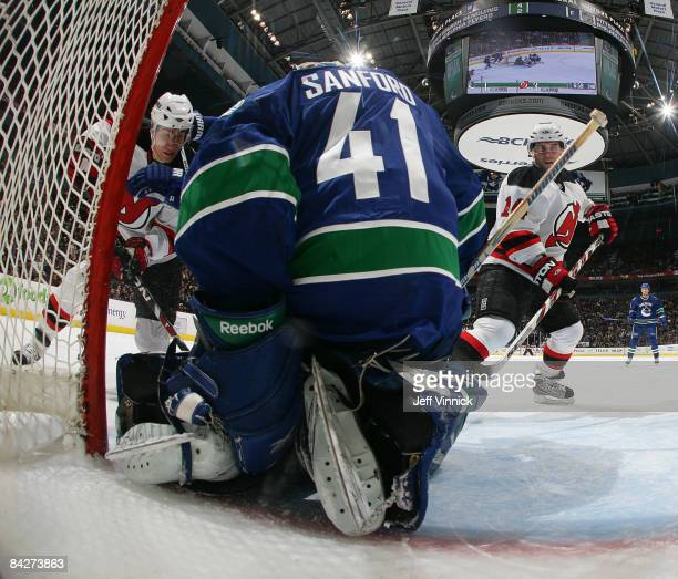Brian Gionta of the New Jersey Devils and teammate Dainius Zubrus watch on as Curtis Sanford of the Vancouver Canucks makes a save during their game...