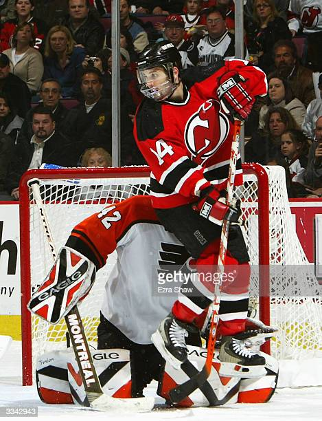 Brian Gionta of the New Jersey Devils jumps in front of the Philadelphia Flyers goalie Robert Esche to block his view of a shot taken by Patrik Elias...
