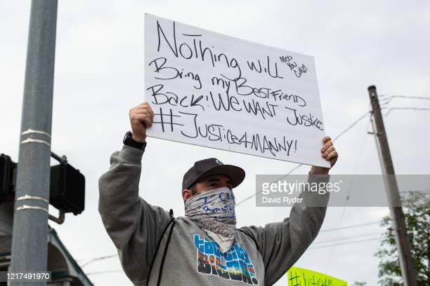 Brian Giordano holds a sign during a vigil for his best friend Manuel Ellis a black man whose March death while in Tacoma Police custody was recently...