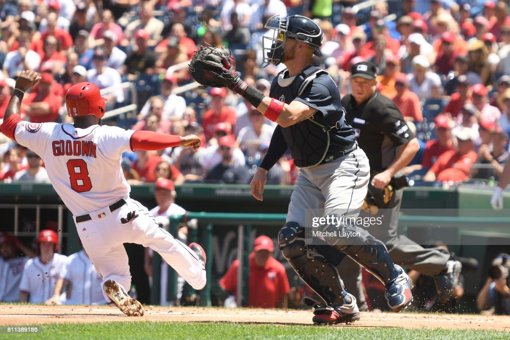 Brian Goodwin #8 of the Washington Nationals slides safely past Tyler Flowers #25 of the Atlanta Braves on Ryan Zimmerman #11 (not pictured) sac fly to score the team first run in the first inning during a baseball game at Nationals Park on July 9, 2017 in Washington, DC.
