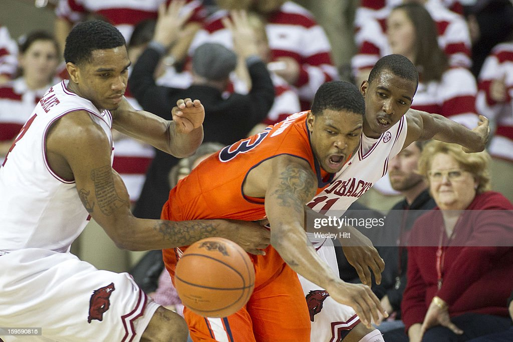 Brian Greene Jr. #23 of the Auburn Tigers goes after a loose ball against Coty Clarke #4 and BJ Young #11 of the Arkansas Razorbacks at Bud Walton Arena on January 16, 2013 in Fayetteville, Arkansas. The Razorbacks defeated the Tigers 88-80.
