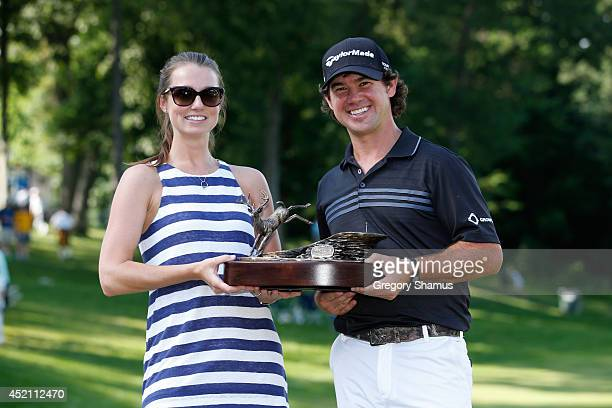 Brian Harman holds the trophy with his fiance Kelly Van Slyke after winning the John Deere Classic held at TPC Deere Run on July 13 2014 in Silvis...