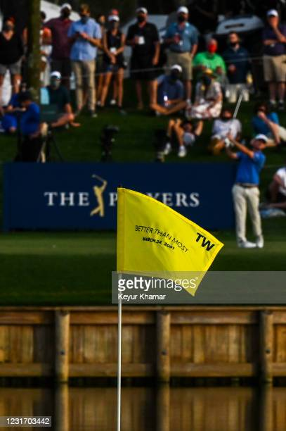 Brian Harman plays his tee shot to a pin flag with the text Better Than Most to commemorate a putt by Tiger Woods on the 17th hole during the third...