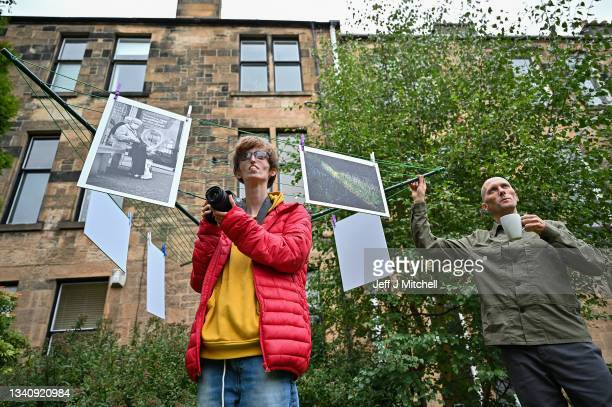"""Brian Hartley and Dylan Lombard pose beside their photographic exhibition in a tenement garden on September 17, 2021 in Glasgow, Scotland. """"Stills of..."""