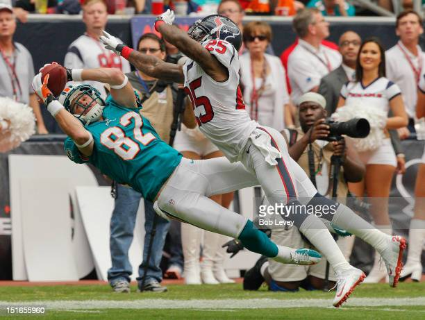 Brian Hartline of the Miami Dolphins completes a reception as he beats Kareem Jackson of the Houston Texans on the play during the season opener at...