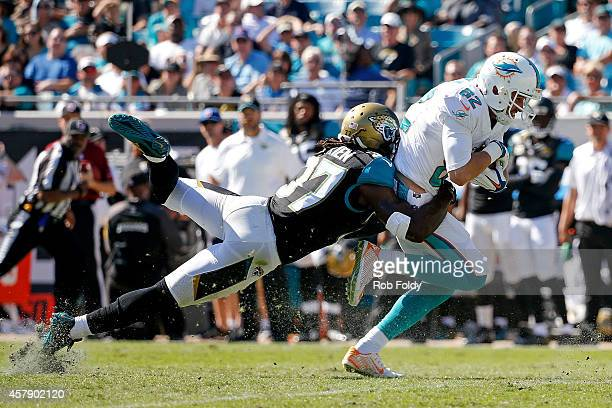 Brian Hartline of the Miami Dolphins is brought down by Johnathan Cyprien of the Jacksonville Jaguars during the first half of the game at EverBank...