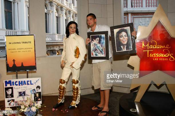 Brian Henderson of Washington holds images of Michael Jackson as he poses for photos next to a wax figure of Jackson outside Madame Tussauds Las...