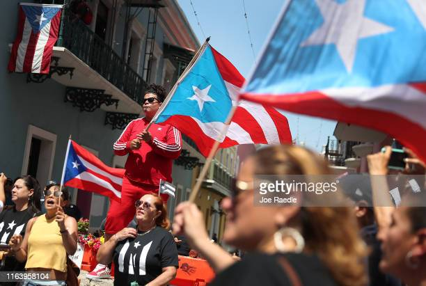 Brian Hernandez waves a Puerto Rican flag from a top a police barricade on a street leading to the Governor's Mansion as reports persist that Ricardo...