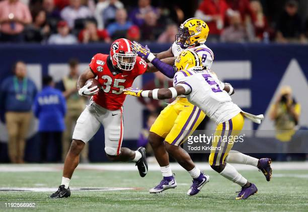 Brian Herrien of the Georgia Bulldogs runs with the ball as Kary Vincent Jr #5 and Patrick Queen of the LSU Tigers attempt to tackle him in the first...