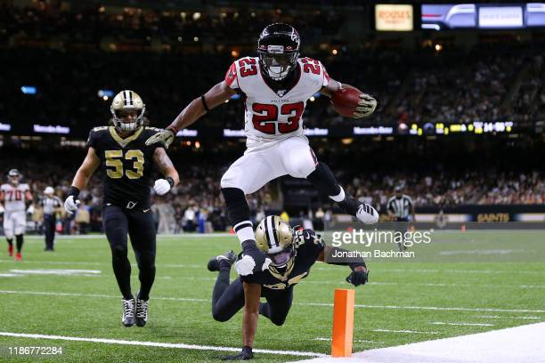 Brian Hill of the Atlanta Falcons scores a touchdown as Eli Apple of the New Orleans Saints and AJ Klein defends during the second half of a game at...
