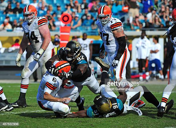 Brian Hoyer of the Cleveland Browns is sacked by Ziggy Hood and Chris Clemons of the Jacksonville Jaguars at EverBank Field on October 19 2014 in...