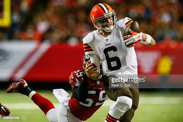 Brian Hoyer of the Cleveland Browns loses the ball out of bounds under pressure by Joplo Bartu of the Atlanta Falcons in the first half at Georgia...