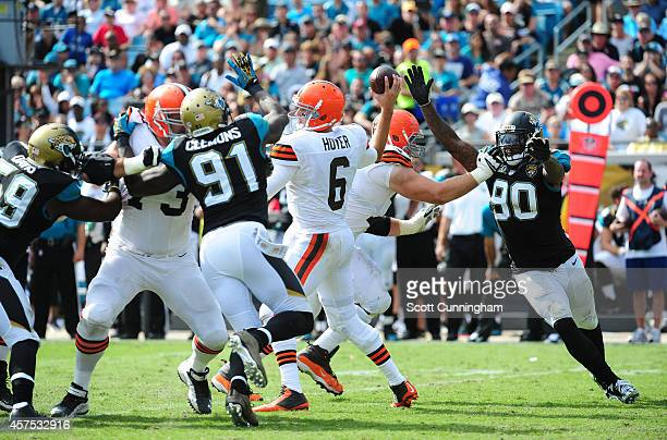 Brian Hoyer of the Cleveland Browns passes despite pressure by Chris Clemons and Andre Branch of the Jacksonville Jaguars at EverBank Field on...