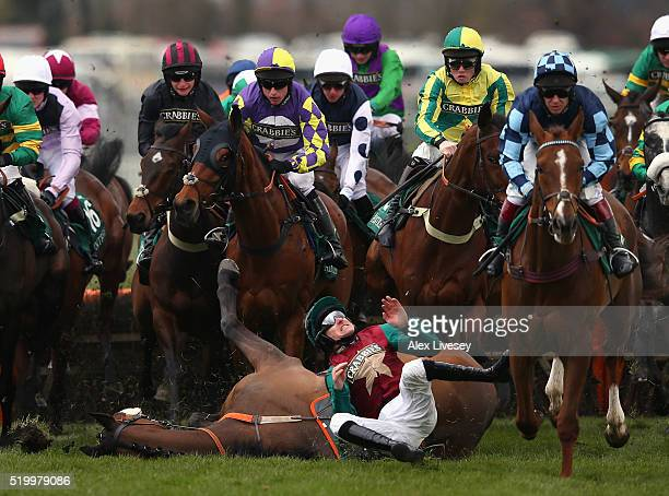 Brian Hughes falls from Urban Hymn after jumpoing the first fence during the Gaskells Waste Management Handicap Hurdle at Aintree Racecourse on April...