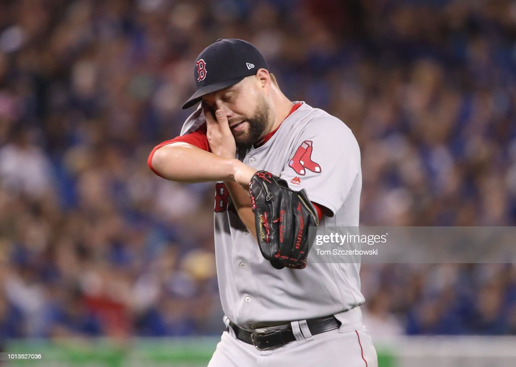 Brian Johnson #61 of the Boston Red Sox walks off the mound to the dugout after getting the last out of the seventh inning in which he gave up a three-run home run against the Toronto Blue Jays at Rogers Centre on August 8, 2018 in Toronto, Canada.