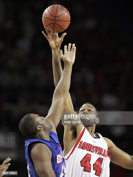 Brian Johnson of the Louisville Cardinals reaches for the ball against Marlon Brumfield of the DePaul Blue Demons on the opening jump ball during the...