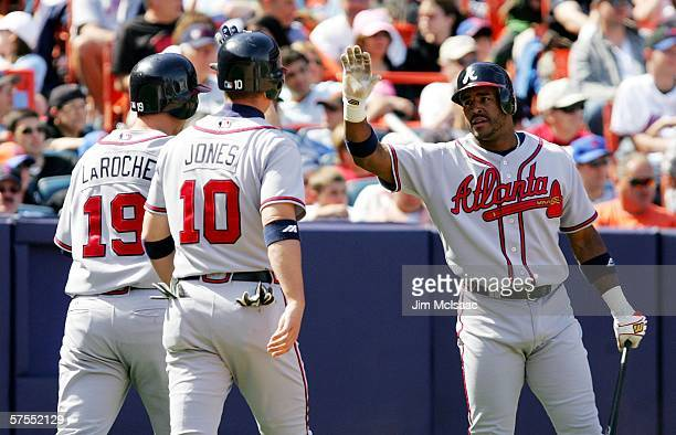 Brian Jordan of the Atlanta Braves greets teammates Adam LaRoche and Chipper Jones after they scored on a base hit from Brian McCann against the New...