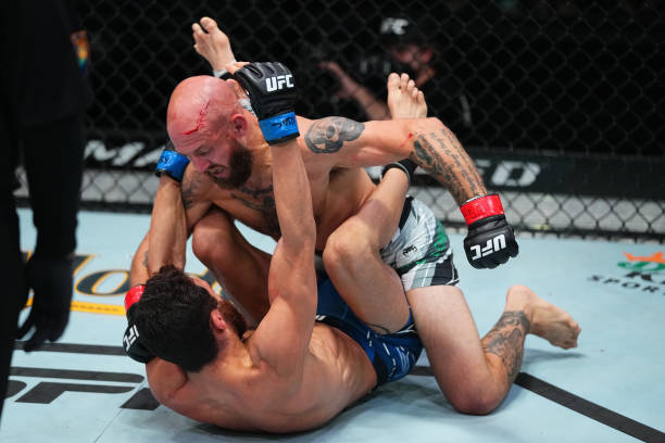 Brian Kelleher punches Domingo Pilarte in a bantamweight fight during the UFC Fight Night event at UFC APEX on August 21, 2021 in Las Vegas, Nevada.
