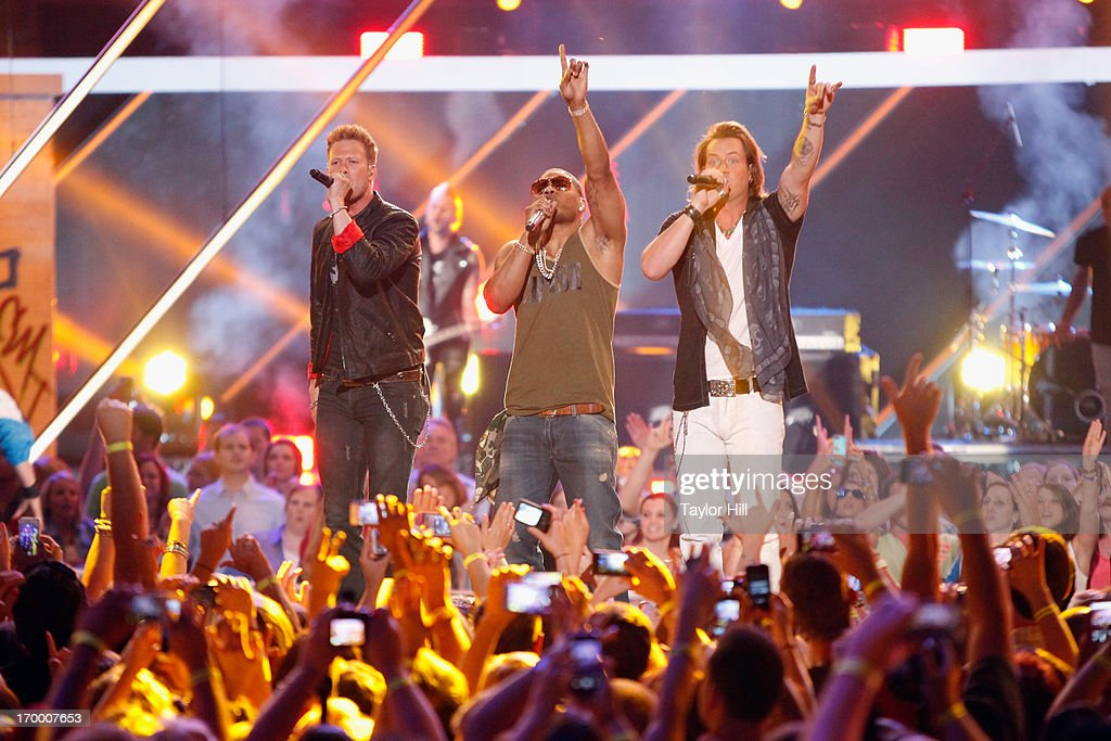 Brian Kelley (L) and Tyloer Hubbard (R) of Florida-Georgia Line and Nelly (C) perform 'Cruise' to close the 2013 CMT Music awards at the Bridgestone Arena on June 5, 2013 in Nashville, Tennessee.