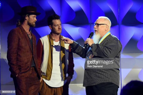 Brian Kelly and Tyler Hubbard of Florida Georgia Line present an award to Spotify's John Marks onstage at the Innovation In Music Awards on June 3...