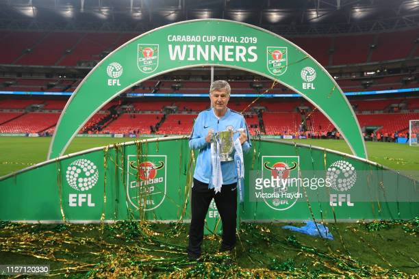 Brian Kidd assistant manager of Manchester City celebrates victory with the trophy after the Carabao Cup Final between Chelsea and Manchester City at...