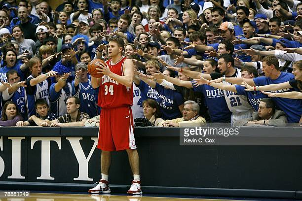 Brian Kreefer of Cornell Big Red looks to move the ball while fans of the Duke Blue Devils attempt to distract him during the college basketball game...