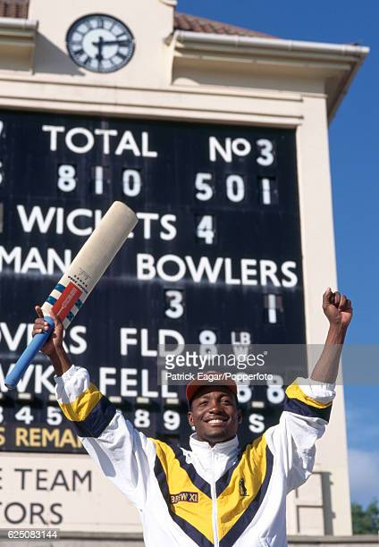 Brian Lara of Warwickshire celebrates his innings of 501 not out in front of the scoreboard at the end of the County Championship match between...