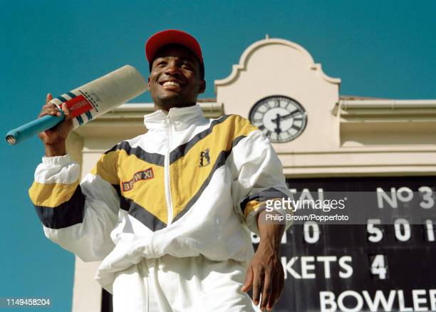 Brian Lara of Warwickshire stands in front of the scoreboard showing his record score of 501 not out at the end of the Britannic Assurance County...