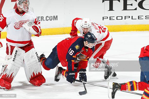 Brian Lashoff of the Detroit Red Wings upends Aleksander Barkov of the Florida Panthers as he skates past goaltender Jimmy Howard at the BBT Center...